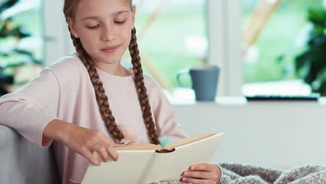 Closeup-Portrait-Girl-9-Years-Old-Reading-Book-In-The-Living-Room