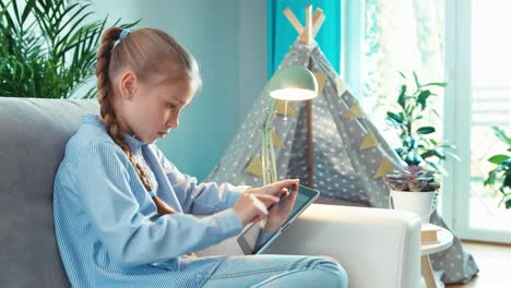Cute-Blonde-Girl-9-Years-Old-Using-Tablet-PC-Surfing-In-Internet