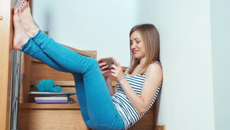 Cute-Woman-Using-Cell-Phone-Sitting-On-The-Stairs