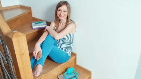 Cute-Young-Woman-Using-Cell-Phone-On-The-Stairs-And-Smiling-Top-View