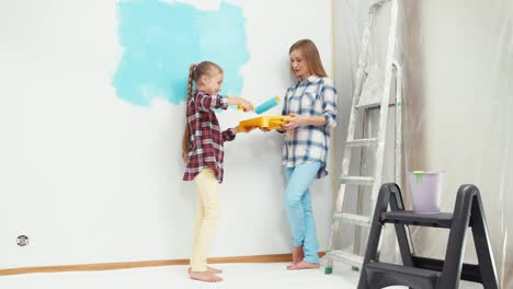 Daughter-Painting-Wall-And-Mother-Holds-In-Her-Hands-Roller-Tray-With-A-Paint