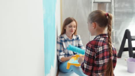Daughter-Painting-Wall-At-Home-And-Mother-Looking-At-Her