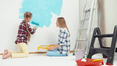 Daughter-Painting-Wall-In-Blue-Color-Mother-Sitting-On-The-Floor-And-Smiling
