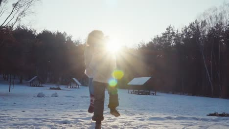 Family-dancing-in-the-snow-in-a-winter-forest