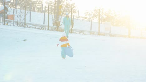 Family-Have-Fun-On-Winter-Hill-Girl-Rides-A-Sledding-Down-On-Snow-Disk