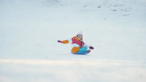 Family-Have-Fun-On-Winter-Hill-Girl-Spinning-On-Snow-Disk-And-Laughing-Again
