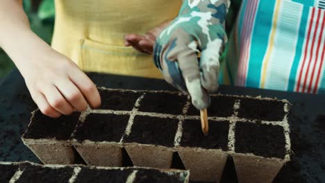 Family-Planting-Seeds-To-Peat-Pot