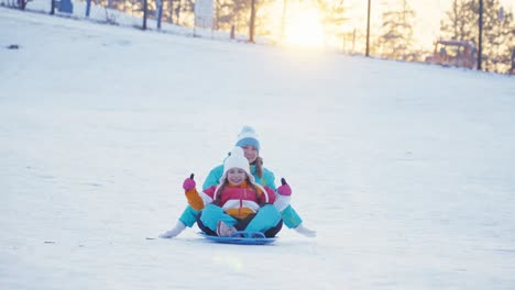 Family-Rides-A-Sledding-Down-On-Snow-Disk-In-Sunny-Day-Against-Sunset