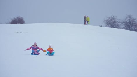 Family-Sliding-Downhill-On-Snow-Disk-In-Wintertime
