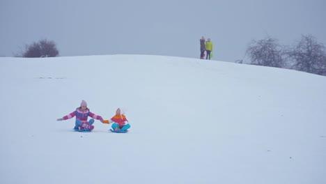 Familia-Deslizándose-Cuesta-Abajo-En-El-Disco-De-Nieve-En-Invierno