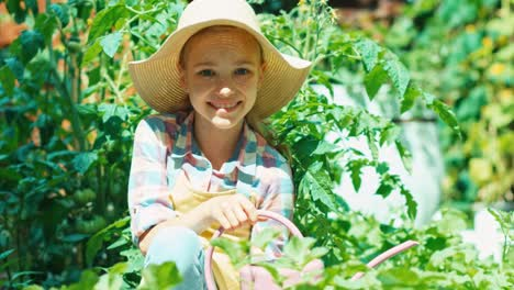 Farmer-Child-Watering-Vegetables-In-Her-Kitchen-Garden-And-Smiling-At-Camera