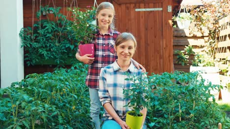 Farmers-Family-Holds-Tomatoes-In-The-Pots-In-Garden-And-Smiling-At-Camera