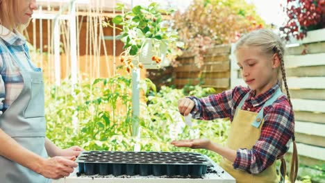 Farmers-Mother-And-Daughter-Plants-Seeds-To-Soil