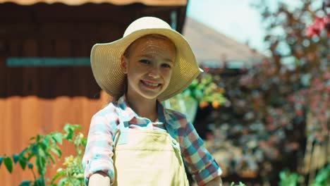 Girl-8-Age-Holds-Watering-Can-And-Smiling-At-Camera-In-The-Garden