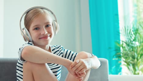 Girl-8-Age-Listening-Music-With-Headphones-And-Smiling-At-Camera-Child-Sitting