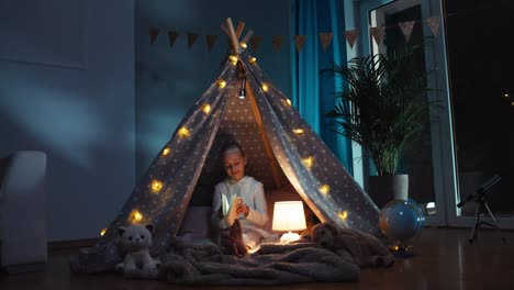 Girl-9-Years-Old-Opens-Book-And-Reading-It-At-Night-In-The-Wigwam