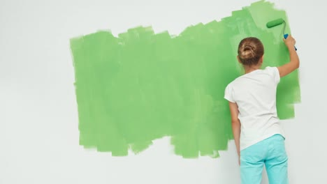 Girl-9-Years-Old-Painting-Wall-In-Apartment-In-Color-Green-And-Smiling-At-Cam