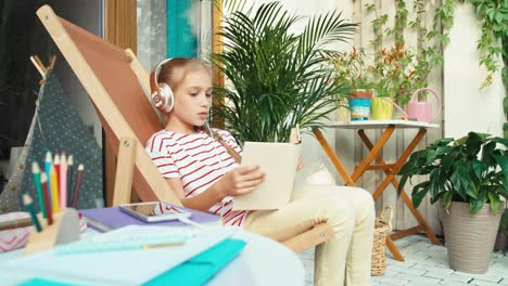 Girl-9-Years-Old-Reading-Book-And-Listening-Music-On-Patio-At-Home
