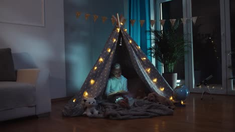 Girl-9-Years-Old-Reading-Book-At-Night-In-The-Wigwam