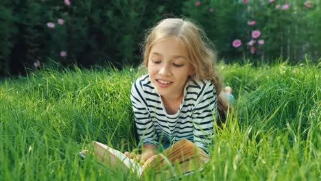 Girl-9-Years-Old-Reading-Book-Lying-In-Green-Grass-And-Smiling-At-Camera