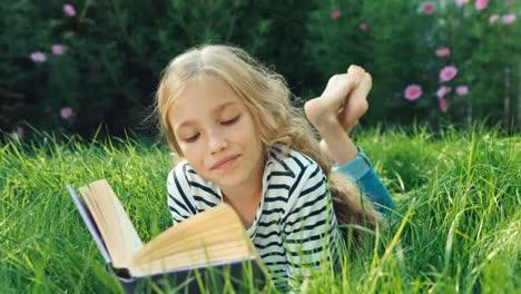 Niña-De-9-Años-Leyendo-Libro-Infantil-Tumbado-En-La-Hierba-Verde-Dolly-Shot