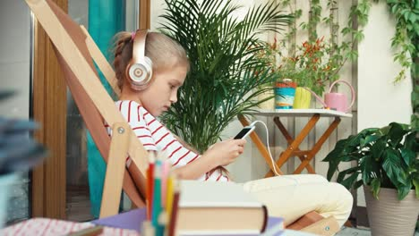 Girl-9-Years-Old-Using-Cell-Phone-On-Patio-At-Home
