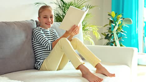 Girl-9-Years-Reading-Book-And-Smiling-At-Camera-On-The-Sofa-Dolly-Shot