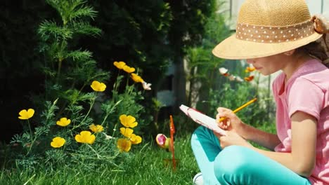 Girl-Aged-8-Looking-Drowing-In-Notebook-And-Sitting-On-The-Grass-In-The-Garden