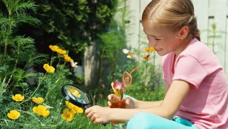 Niña-De-8-Años-Mirando-Con-Lupa-A-La-Flor-Y-Beber-Jugo