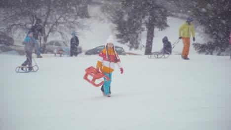 Girl-Catching-Snowflakes-Tongue-And-Walking-At-Camera-With-Sled