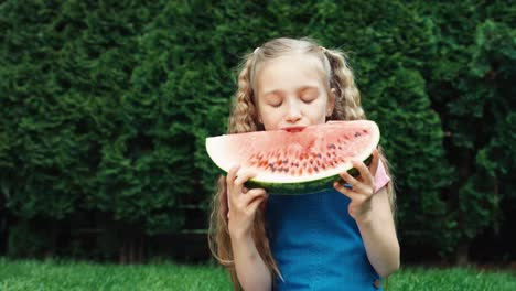 Girl-Child-Bites-A-Piece-Of-Watermelon-And-Smiling-At-Camera-Outdoors