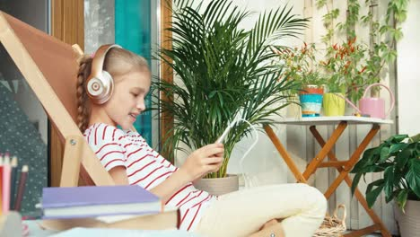 Girl-Niño-Connect-Headphones-To-Cell-Teléfono-And-Listening-Música-And-Smiling