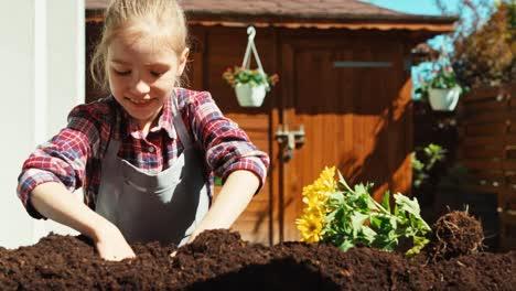 Niña-Plantar-Flores-Y-Sonriendo-A-La-Cámara