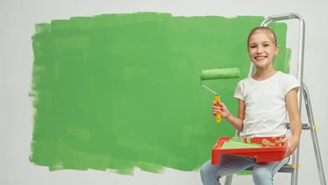 Girl-Child-Sitting-On-Ladder-Near-Wall-Green-Color-Kid-Holds-Paint-Roller