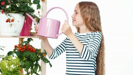 Girl-Child-Watering-Her-Plants-On-White-Background-Child-Standing-Near-Shelf