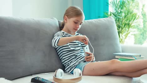 Girl-Connecting-Headphones-To-Cell-Teléfono