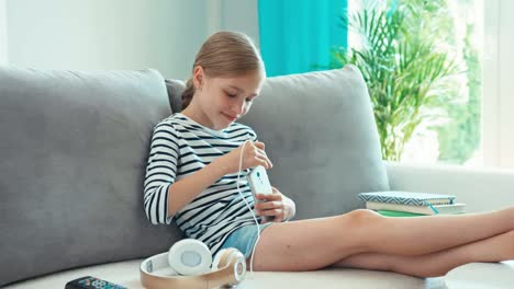 Chica-Conectando-Auriculares-Al-Celular-Y-Escuchando-Música
