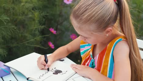Girl-Drawing-Spider-In-The-Notebook