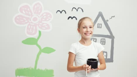 Girl-Holding-Paint-And-Standing-Near-Wall