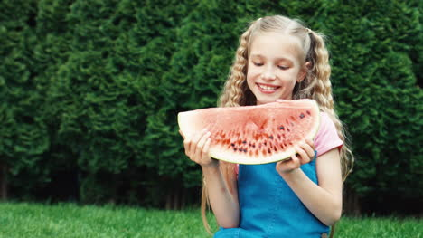 Girl-Holds-A-Piece-Of-Watermelon-And-Smiling-At-Camera-With-Teeth-Outdoors