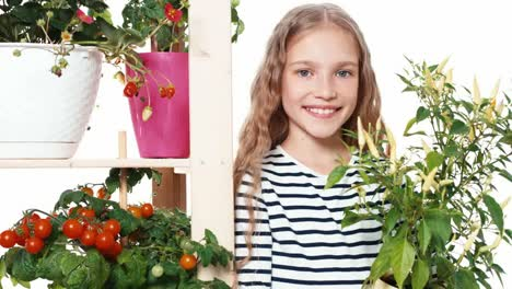 Girl-Holds-Little-Peppers-In-Pot-On-White-Background