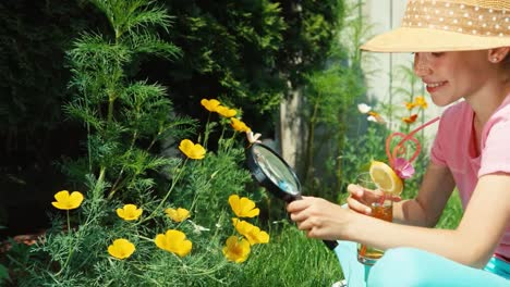 Girl-Holds-Magnifying-Glass-And-Glass-Of-Juice-Outdoors
