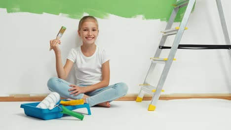 Girl-Holds-Paintbrush-With-Paint-And-Sitting-On-The-Floor-On-The-Background