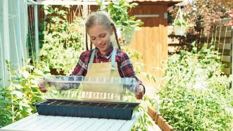 Girl-Holds-Pot-For-Seeds-Of-Vegetables
