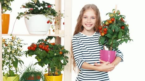 Girl-Holds-Tomatoes-In-Pot-And-Smiling-With-Teeth-At-Camera