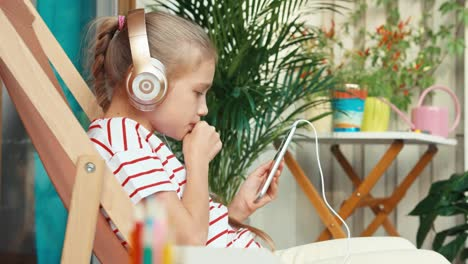 Girl-In-Headphones-Relaxing-Using-Cellphone-On-Patio
