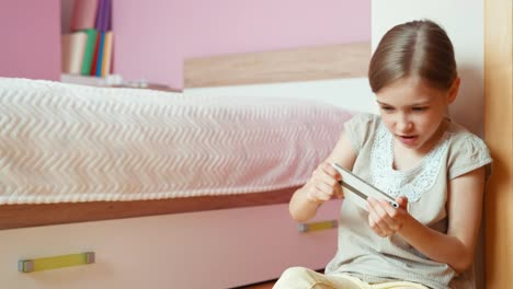Girl-In-The-Bedroom-Playing-To-Online-Game-On-Cell-Teléfono