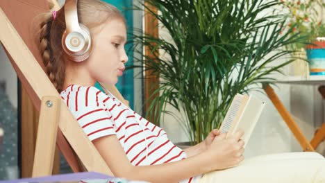 Girl-Listening-Music-In-Headphones-And-Reading-Book-Outdoors-At-Home