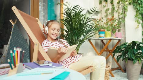 Girl-Listening-Music-In-Headphones-And-Reading-Book