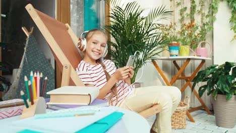 Girl-Listening-Music-In-Headphones-Sitting-On-Chair-Outdoors-At-Home